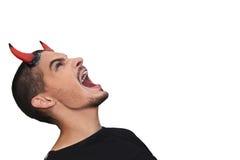Jeune homme avec les klaxons rouges sur le sien chef criant vers le haut Photo stock