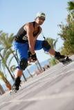 Jeune homme avec les patins intégrés en été extérieur Photographie stock