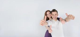 Jeune homme avec son amie montrant des pouces  Photo stock