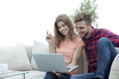 Jeune homme avec son amie observant une émission de TV sur l'ordinateur portable se reposant dans le salon Images stock