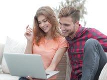Jeune homme avec son amie observant une émission de TV sur l'ordinateur portable se reposant dans le salon Photographie stock libre de droits