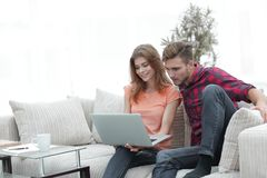 Jeune homme avec son amie regardant l'ordinateur portable se reposant sur le sofa Photo libre de droits