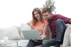 Jeune homme avec son amie regardant l'ordinateur portable se reposant sur le sofa Images stock