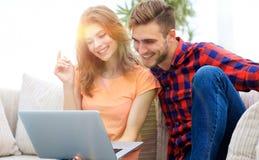 Jeune homme avec son amie regardant l'ordinateur portable se reposant sur le sofa Photo stock