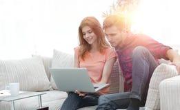 Jeune homme avec son amie regardant l'ordinateur portable se reposant sur le sofa Image libre de droits
