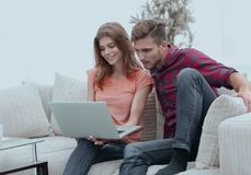 Jeune homme avec son amie regardant l'ordinateur portable se reposant sur le sofa Photographie stock