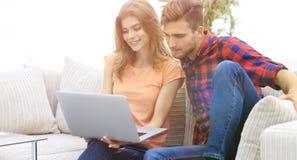 Jeune homme avec son amie regardant l'ordinateur portable se reposant sur t Photos stock