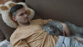 Jeune homme avec son chat pelucheux gris-clair banque de vidéos