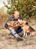 Jeune homme avec son chien sur la clairière ensoleillée de forêt d'automne avec le mushroo Photos stock