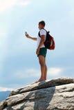 Jeune homme avec tenir et prendre le selfie sur une montagne Photographie stock