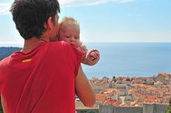 Jeune homme avec un bébé regardant Dubrovnik Image stock