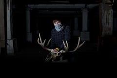 Jeune homme avec un crâne de cerfs communs devant lui dans la cave foncée photos libres de droits
