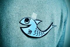 Jeune homme avec un poisson de papier attaché au sien de retour Photo libre de droits