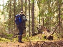 Jeune homme avec un sac à dos augmentant dans une forêt Image stock
