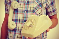 Jeune homme avec un téléphone de cadran rotatoire, avec un rétro effet Images libres de droits