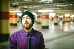 Jeune homme avec une barbe dans une chemise de plaid et un lien et un chapeau photos libres de droits