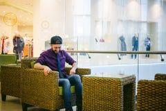 Jeune homme avec une barbe dans une chemise de plaid et un lien et un chapeau photographie stock