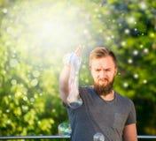 Jeune homme avec une barbe passant le temps en nature, faisant le fond de nature de bulles de savon avec le bokeh image stock