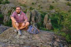 Jeune homme avec une barbe se reposant sur la falaise de canyon Photo stock