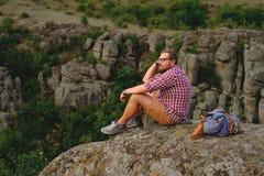 Jeune homme avec une barbe se reposant sur la falaise de canyon Photos stock