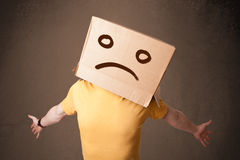 Jeune homme avec une boîte en carton brune sur sa tête avec le visage triste Images stock