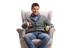 Jeune homme avec une bouteille à télécommande et à bière dans un fauteuil images libres de droits