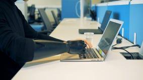 Jeune homme avec une main de cyborg travaillant sur l'ordinateur 4K banque de vidéos