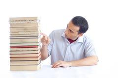 Jeune homme avec une pile des livres Photographie stock