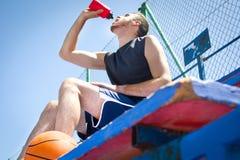 Jeune homme avec une séance d'eau potable de basket-ball photo stock