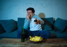 Jeune homme ayant l'amusement à la maison observant le film d'horreur à la TV la nuit photo libre de droits