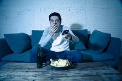 Jeune homme ayant l'amusement à la maison observant le film d'horreur à la TV la nuit photos libres de droits