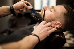 Jeune homme ayant la barbe équilibrée au salon de coiffeur image stock