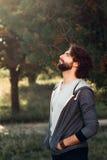 Jeune homme ayant le bain de soleil dans la forêt, vue de côté Photo stock
