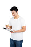 Jeune homme ayant le café et lisant le journal Photos libres de droits