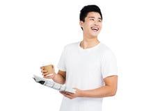 Jeune homme ayant le café et lisant le journal Image stock