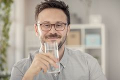 Jeune homme ayant le verre de l'eau Image libre de droits