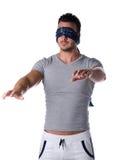 Jeune homme bandé les yeux sentant sa manière dans l'obscurité Image libre de droits