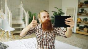 Jeune homme barbu à l'aide de la tablette ayant la causerie visuelle se reposant dans le lit à la maison Photo stock