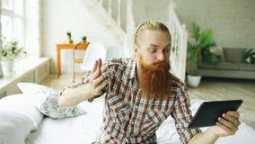 Jeune homme barbu à l'aide de la tablette ayant la causerie visuelle se reposant dans le lit à la maison Images libres de droits