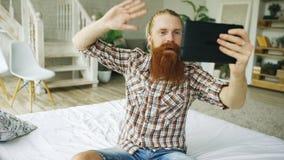 Jeune homme barbu à l'aide de la tablette ayant la causerie visuelle se reposant dans le lit à la maison Images stock