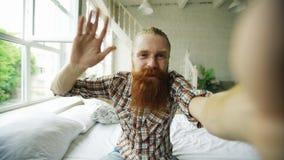 Jeune homme barbu à l'aide de la tablette ayant la causerie visuelle se reposant dans le lit à la maison Photographie stock