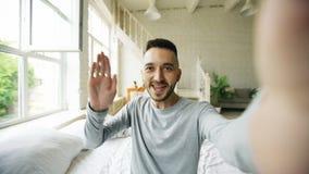 Jeune homme barbu à l'aide de la tablette ayant la causerie visuelle se reposant dans le lit à la maison Image libre de droits