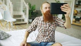 Jeune homme barbu à l'aide de la tablette ayant la causerie visuelle se reposant dans le lit à la maison Photos libres de droits