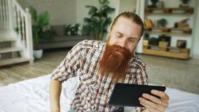 Jeune homme barbu à l'aide de la tablette ayant la causerie visuelle se reposant dans le lit à la maison Photo libre de droits