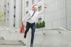 Jeune homme barbu adulte dans le chapeau de Santa tenant beaucoup de paniers et de cadeaux et de fonctionnement sur des enfants Photo stock