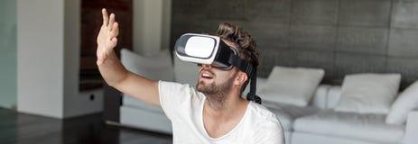 Jeune homme barbu avec l'interface imaginaire émouvante i en verre de VR Photos libres de droits