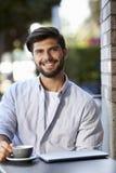 Jeune homme barbu avec l'ordinateur portable se reposant en dehors du café, vertical photo libre de droits