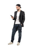 Jeune homme barbu avec le chapeau arrière utilisant le dispositif de téléphone portable Images stock