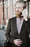 Jeune homme barbu avec le mobile, extérieur Photographie stock libre de droits