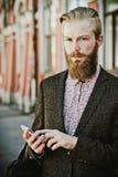 Jeune homme barbu avec le mobile, extérieur Photos stock
